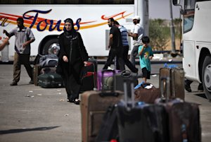 Palestinians wait with their luggage near buses to …