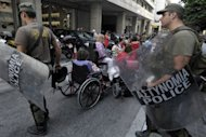 Disabled people protest on September 13, against cuts in their allowances in front of the Finance Ministry in Athens. Eurogroup finance ministers converged Friday around a growing consensus to give Athens &quot;more time&quot; to meet economic targets under its delayed bailout, although hardliners insisted there would be any &quot;extra money&quot;