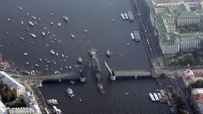 "An aerial view shows tug boats towing the ""Cruiser Aurora"" along the Neva River in central part of St. Petersburg"