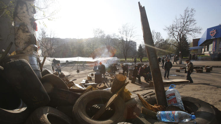 People gather in front of a barricade across a street in Slovyansk, eastern Ukraine, Wednesday, April 16, 2014. The city of Slovyansk has come under the increasing control of the pro-Russian gunmen who seized it last weekend. (AP Photo/Sergei Grits)