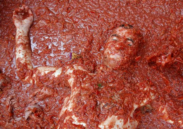"A reveler lays in tomato pulp during the annual ""Tomatina"" tomato fight fiesta in the village of Bunol, near Valencia, Spain, Wednesday, Aug. 31, 2011. Bunol's town hall estimated more than 40,000 peo"