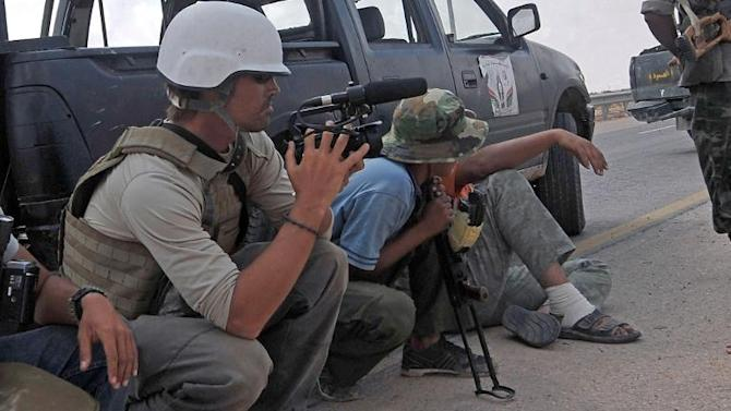 File picture taken on September 29, 2011 shows US freelance reporter James Foley (L) on the highway between the airport and the West Gate of Sirte, Libya