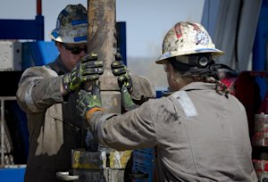 Workers change pipes at a rig exploring the Marcellus …