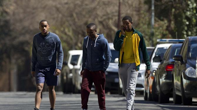 Grandsons Andile Mandela, left, walks with brother Mbuso, right, and unidentified man, outside their grandfather's, former South African President Nelson Mandela's house in Johannesburg, South Africa Monday, Sept. 2, 2013. South Africans on Monday welcomed Nelson Mandela's discharge from a hospital after nearly three months of treatment amid concerns that his health remains so poor that he still must receive intensive care at home. (AP Photo/Themba Hadebe)