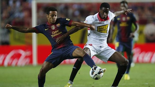 Barcelona's Thiago Alcantara (L) fight for the with ball Sevilla's Geoffrey Kondogbia