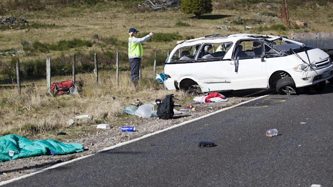 Policemen examine the scene of a minivan crash near Turangi, New Zealand, Saturday, May 12, 2012. Three Boston University students who were studying in New Zealand were killed Saturday when their minivan crashed. At least five other students from the university were injured in the accident, including one who was in critical condition. (AP Photo/New Zealand Herald, John Cowpland)