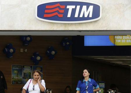 A woman speaks on a mobile phone next to an attendant at a Telecom Italia Mobile (TIM) store in downtown Rio de Janeiro
