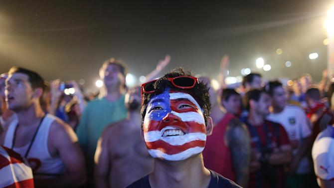 A soccer fan of the U.S. national soccer team watches a live broadcast of the soccer World Cup match between USA and Ghana, inside the FIFA Fan Fest area on Copacabana beach, Rio de Janeiro, Brazil, Monday, June 16, 2014
