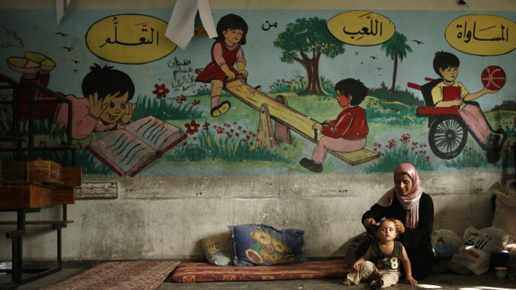 A Palestinian woman, who fled her house that is adjacent to the border with Israel, combs her daughter's hair as they stay at a United Nations-run school in Gaza City