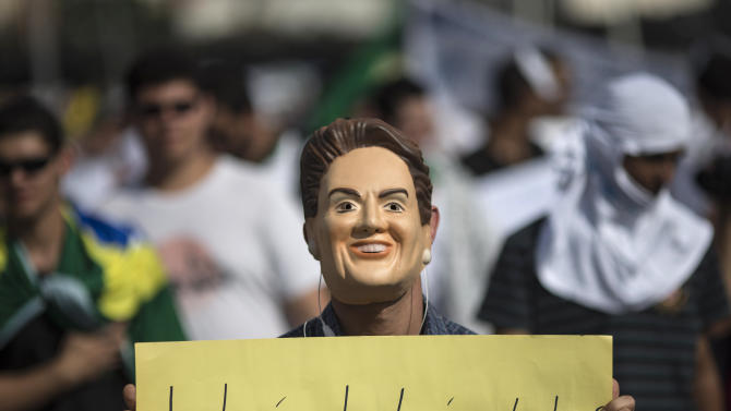 FILE - In this June 22, 2013 file photo, a man wearing a mask depicting Brazilian President Dilma Rousseff, holds a banner criticizing her yesterday speech during a protest in Belo Horizonte, Brazil. Public approval of Brazilian President Dilma Rousseff's government has suffered a steep drop since protesters calling for a wide-range of reforms took to the streets all over Brazil in the past two weeks, according to Brazil's first nationwide poll released since the unrest began. (AP Photo/Felipe Dana, File)