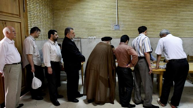 In this Friday, June 12, 2009 photo, Iranian men line up to get ballots for the presidential elections at a polling station, in Tehran, Iran. Elections to pick Iran's next president are still five months away, but that's not too early for some warning shots by the country's leadership. The message to anyone questioning the openness of the June vote: Keep quiet. (AP Photo/Vahid Salemi)