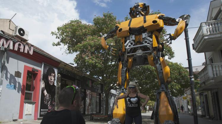 "Man takes a picture of his girlfriend in front of ""Bobo"", a ""Transformers-inspired"" sculpture constructed from scrap metal in Podgorica"