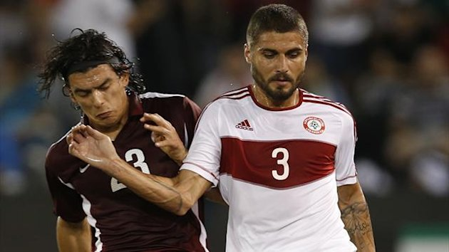 Lebanon's Yousef Mohammed fights for the ball with Qatar's Sebastian Soria during their 2014 World Cup qualifying soccer match in Doha