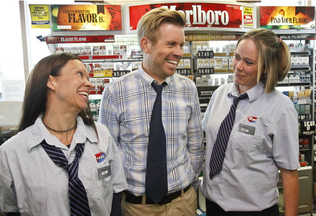 Store owner Eric Seitz, middle, laughs along with cashiers Tina Long, left, and Candy Browning at a 4 Sons Food Store where one of the winning tickets in the $579.9 million Powerball jackpot was purch