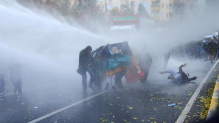 A Kurdish protester falls to the ground as Turkish riot police use water cannons to disperse them during a demonstration in Diyarbakir on December 8, 2013