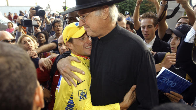 FILE - In this July 27, 2003, file photo, Edward Lee Walker, president of the Lance Armstrong Foundation, right, greets winner Lance Armstrong after the 20th and final stage of the Tour de France cycling race in Paris. Armstrong was diagnosed with cancer in 1996. After undergoing chemotherapy and having the tumors removed from his brain he was declared cancer-free in 1997. The Livestrong Foundation, formerly known as the Lance Armstrong Foundation, is a nonprofit organization Armstrong founded in 1997 that provides support for people affected by cancer. (AP Photo/Christophe Ena, File)