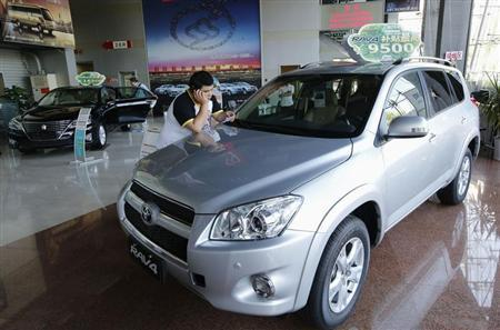 A man uses mobile phone at showroom of Toyota Motor in Beijing