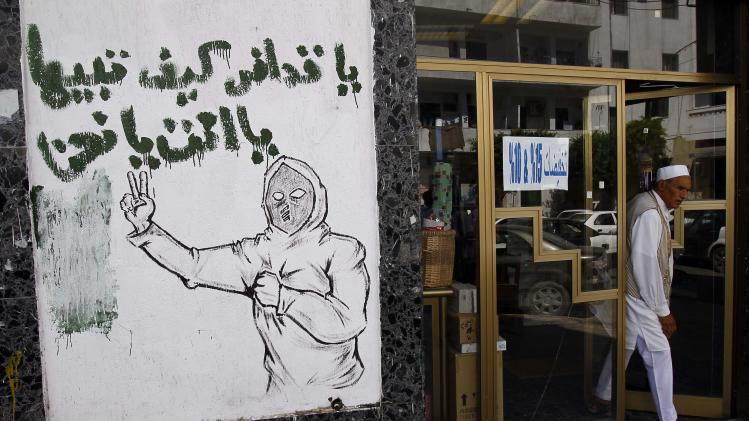 "A graffiti reading  ""Hey Gadhafi, for Libya it is either you or US"" is seen in the streets in Tripoli, Libya, Tuesday, Sept. 20, 2011.   Libyan graffiti artists are taking advantage of newfound freedom to make fun of ousted leader Moammar Gadhafi on the streets of Tripoli, after 42-years of authoritarian rule artists are able to express themselves in public spaces.(AP Photo/Francois Mori)"