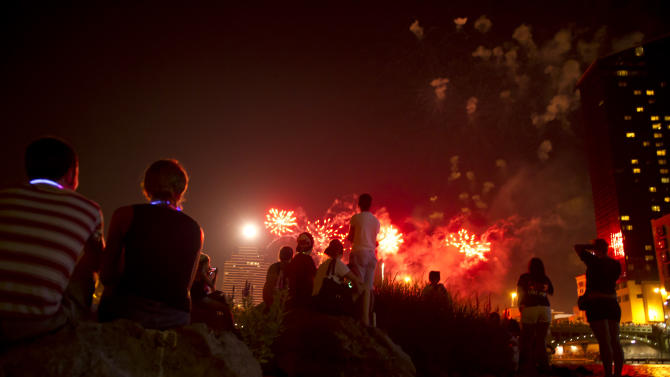 People stand and watch on the small island in the Grand River as fireworks go off above Grand Rapids, Mich on Wednesday, July 4, 2012. (AP Photo/Matthew Busch, The Press)