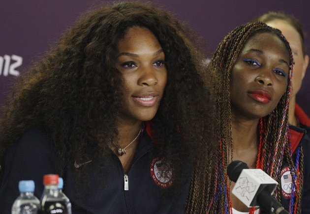 American tennis player Serena Williams, left, responds to questions as Venus Williams looks on during a news conference before the start of the Olympic Games Tuesday, July 24, 2012, in London. (AP Photo/Frank Franklin II)