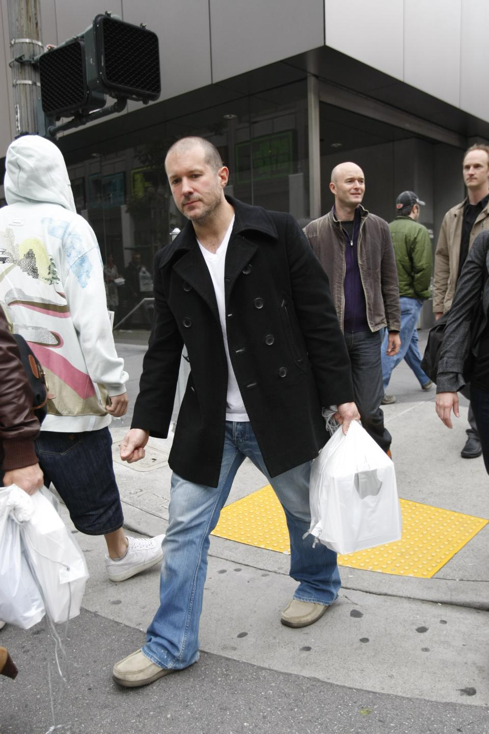 In this April 3, 2010 photo, shows Jonathan Ive, center, Apple senior vice president of Industrial Design, leaving an Apple store in San Francisco on the first day of Apple iPad sales in San Francisco. (AP Photo/Paul Sakuma)