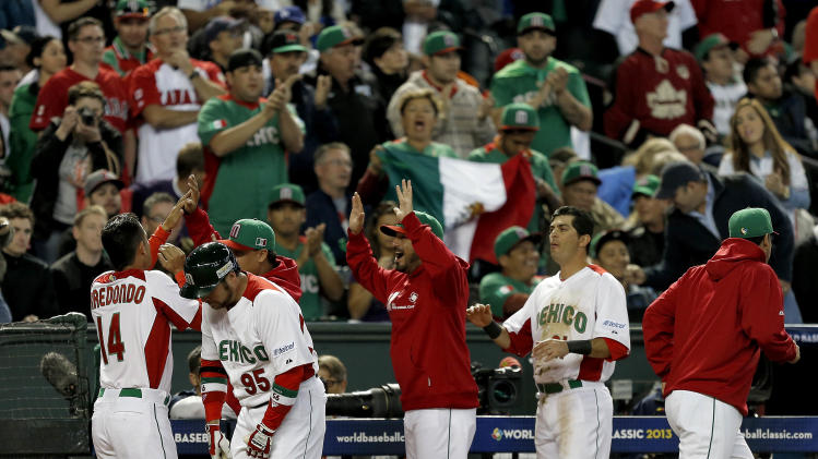 Mexico's Eduardo Arredondo (14) is congratulated by teammates after scoring on a hit by Adrian Gonzalez during the first inning of a World Baseball Classic game against Canada, Saturday, March 9, 2013, in Phoenix. (AP Photo/Matt York)