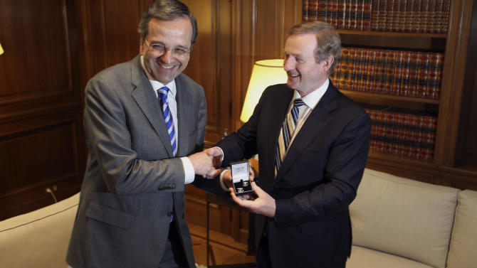 "Greece's Prime Minister Antonis Samaras, left, laughs as he receives a gift, a pair of cufflinks, from his Irish counterpart Enda Kenny during their meeting at Maximos Mansion in Athens, Thursday, May 23, 2013.  Samaras said that Greece would follow the ""same successful model"" as Ireland both of the EU presidency and to exit the crisis. Ireland's EU presidency will finish in the end of June. Greece is scheduled to take over the EU's rotating six-month presidency in January 2014. (AP Photo/Thanassis Stavrakis)"
