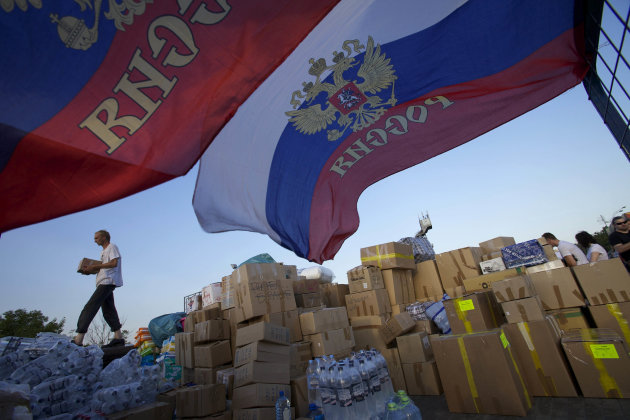 FILE - In this July 9, 2012 file photo, a man carries a food box where people are collecting supplies to be sent to Krymsk for flood victims, in Moscow. At least 171 people died in Krymsk and nearby p