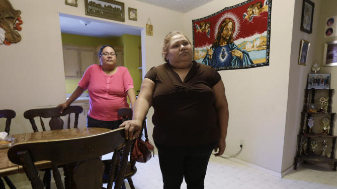 In this July 12, 2012 photo, Rosario Perez, left, and sister, Andrea Gallegos, stand inside a family home, in Brownsville, Texas. Both are without health insurance and have battled cancer. Texas already has one of the nation's most restrictive Medicaid programs, offering coverage only to the disabled, children and parents who earn less than $2,256 a year for a family of three. Without a Medicaid expansion, the state's working poor will continue relying on emergency rooms _ the most costly treatment option _ instead of primary care doctors. The Texas Hospital Association estimates that care for uninsured patients cost hospitals in the state $4.5 billion in 2010. (AP Photo/Eric Gay)