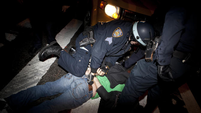 An Occupy Wall Street protester is detained by police officers after being ordered to leave Zuccotti Park, their longtime encampment in New York, early Tuesday, Nov. 15, 2011. At about 1 a.m. Tuesday, police handed out notices from the park's owner, Brookfield Office Properties, and the city saying that the park had to be cleared because it had become unsanitary and hazardous. Protesters were told they could return, but without sleeping bags, tarps or tents. (AP Photo/John Minchillo)