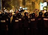 Egyptian riot police stand guard as protesters gather while US Secretary of State Hillary Clinton attends a flag-raising ceremony at the US Consulate General in the mediterranean city of Alexandria