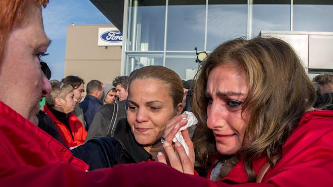 Ford workers react after the European Ford management announced it would close the Ford plant in Genk, Belgium on Wednesday Oct. 24, 2012. A union leader says Ford has decided to close its factory in Genk, Belgium, at the end of 2014 in a move that will result in 4,500 direct job losses and 5,000 more among subcontractors. (AP Photo/Geert Vanden Wijngaert)