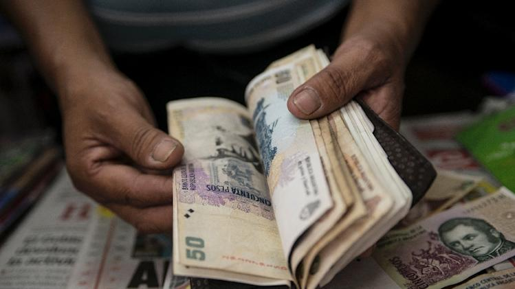 A newsstand owner counts Argentine pesos bills in Buenos Aires on January 24, 2014