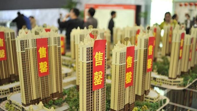 Customers visit a real estate exhibition displaying models of apartments in Hefei