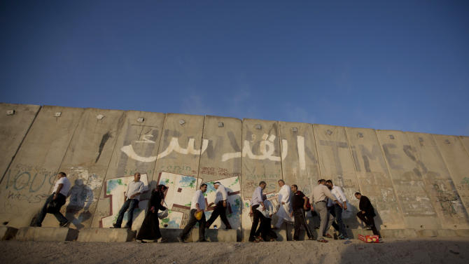 """Palestinian men walk past a section of Israel's separation barrier with Arabic graffiti reading """"Jerusalem"""" to cross the Qalandia checkpoint on their way to pray at the Al-Aqsa Mosque in Jerusalem, on the third Friday of the Muslim holy month of Ramadan, at the Qalandia checkpoint, Friday, July 3, 2015.(AP Photo/Majdi Mohammed)"""
