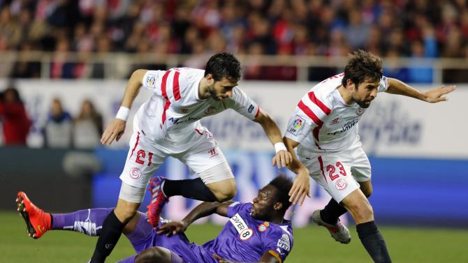 "Sevilla's Pareja and Sevilla's ""Coke"" jump over Espanyol's Caicedo during their soccer match in Seville"