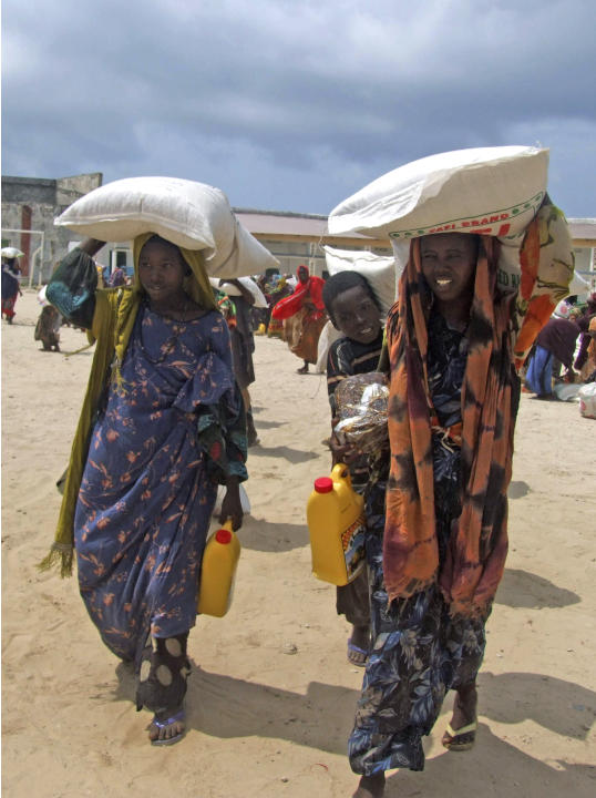 Somali women from southern Somalia walk after receiving rations at a displaced camp in Mogadishu, Somalia, Wednesday, July 20, 2011. Parts of southern Somalia are suffering from famine, a U.N. officia