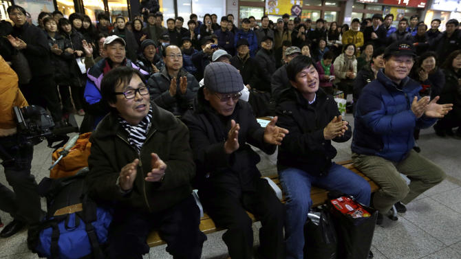 South Koreans cheer as they watch a television broadcast of the country's first rocket launch at Seoul Railway Station in Seoul, South Korea, Wednesday, Jan. 30, 2013. South Korea has launched a rocket in its third attempt to place a satellite in space from its own soil. (AP Photo/Lee Jin-man)