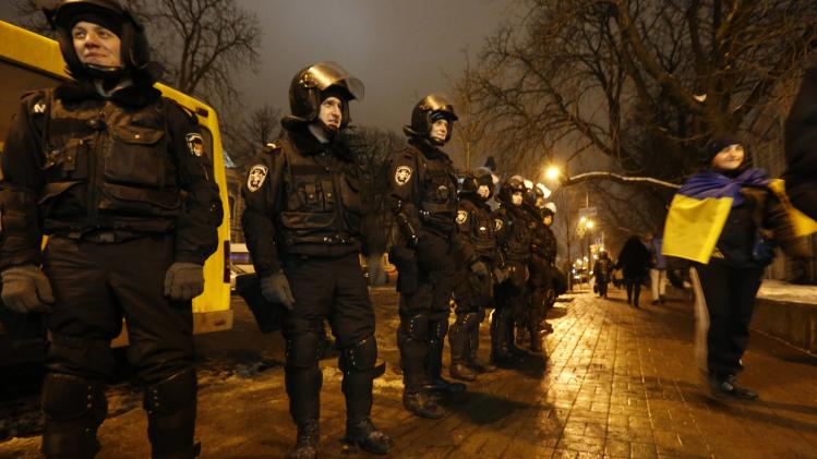 A Pro-European integration protestor wears a Ukrainian flag as he walks in front a police line in central Kiev