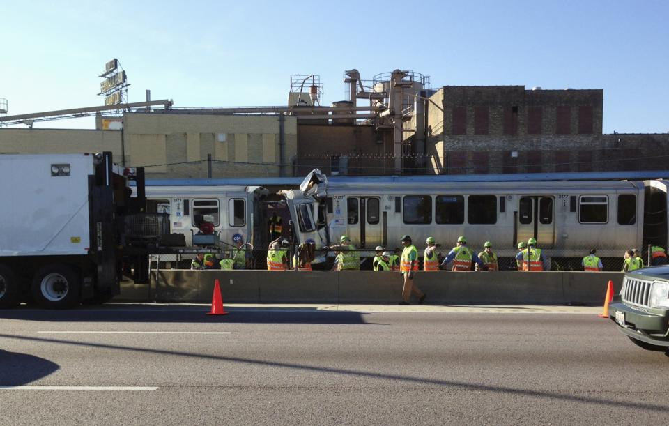 Emergency personnel work at the scene where two Chicago Transit Authority trains collided during rush hour Monday, Sept. 30, 2013, in Forest Park, Ill. About four dozen people were injured in the accident. None were serious.(AP Photo/Don Babwin)