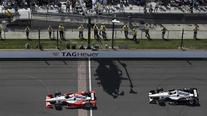 Juan Pablo Montoya, of Colombia, takes the checkered flags ahead of Will Power, of Australia, to win the 99th running of the Indianapolis 500 auto race at Indianapolis Motor Speedway in Indianapolis, Sunday, May 24, 2015.  (AP Photo/Michael Conroy)