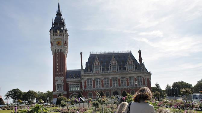 In this Friday, July 31, 2015 photo, people walk past the City Hall of Calais, France. Calais, with its huge port bringing visitors across the Channel by ferry, its Eurostar train which stops in nearby Frethun and its highways, is a natural hub for travelers, but they are going somewhere else. (AP Photo/Thibault Camus)