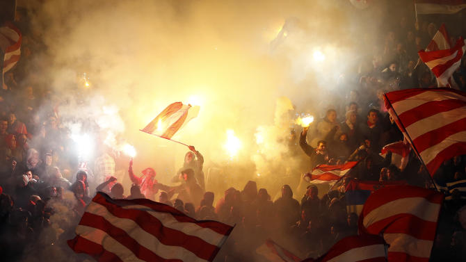 Red Star fans light flares as they cheer for their team during their Serbian Superleague soccer match against Partizan Belgrade in Belgrade