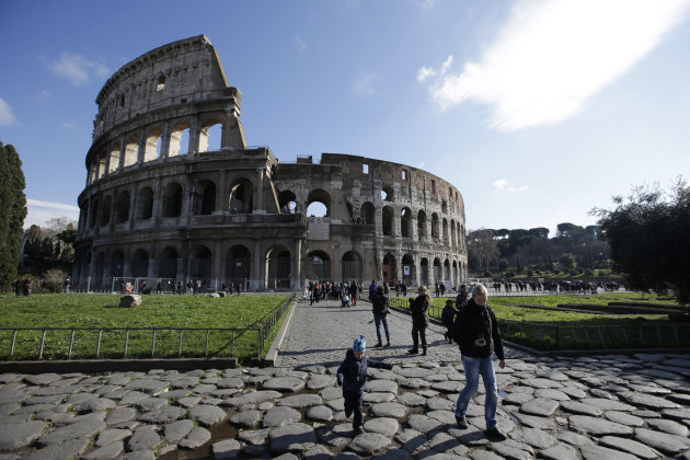 Tourists walk outside Rome's Colosseum, Friday, Jan. 18, 2013. A long-delayed restoration of the Colosseum's only intact internal passageway has yielded ancient traces of red, black and blue frescoes