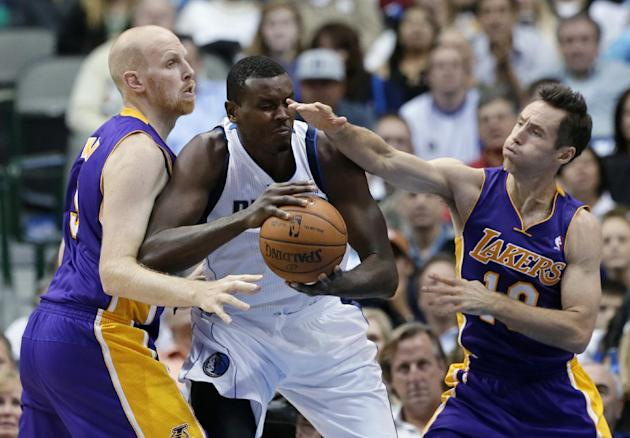 Los Angeles Lakers' Chris Kaman, left, and Steve Nash, right, defend as Dallas Mavericks' Samuel Dalembert of Haiti looks for a shot opportunity in the first half of an NBA basketball game, Tuesday, N