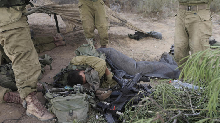 An Israeli soldier sleeps near the border of Israel and the Gaza Strip Wednesday, July 23, 2014. Israeli troops battled Hamas militants on Wednesday near a southern Gaza Strip town, sending Palestinian residents fleeing, as the U.S. secretary of state presses ahead with top-gear efforts to end the conflict that has killed hundreds of Palestinians and tens of Israelis.(AP Photo/Tsafrir Abayov)
