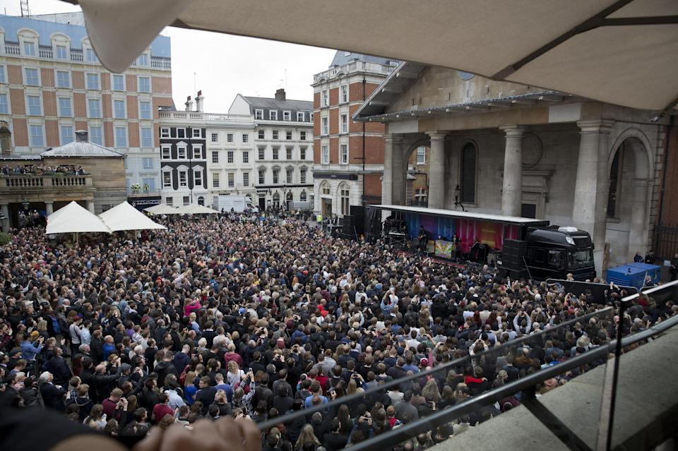 Sir Paul McCartney, center on stage at right, plays a surprise gig in Covent Garden, London, Friday, Oct. 18, 2013. The surprise gig lasted for 20 minutes during lunchtime following a similar appearance in New York last Friday. (AP Photo/Matt Dunham)