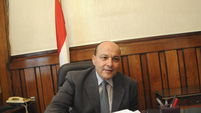 """Newly appointed Egyptian prosecutor general, Talaat Abdullah, sits at his desk on his first day in office after being appointed by President Mohammed Morsi, Satirday, Nov. 24, 2012 in Cairo, Egypt. Morsi fired the controversial former prosecutor general and created """"revolutionary"""" judicial bodies to put Mubarak and some of his top aides on trial a second time for the killings of protesters playing to widespread discontent with the judiciary.(AP Photo/Mohammed Asad)"""