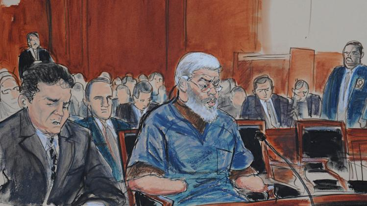 In this courtroom drawing, defense attorney, Jeremy Schneider, left, represents accused terrorist Abu Hamza al-Masri, center, in Manhattan federal court, Tuesday, Oct. 9, 2012, in New York. (AP Photo/ Elizabeth Williams)