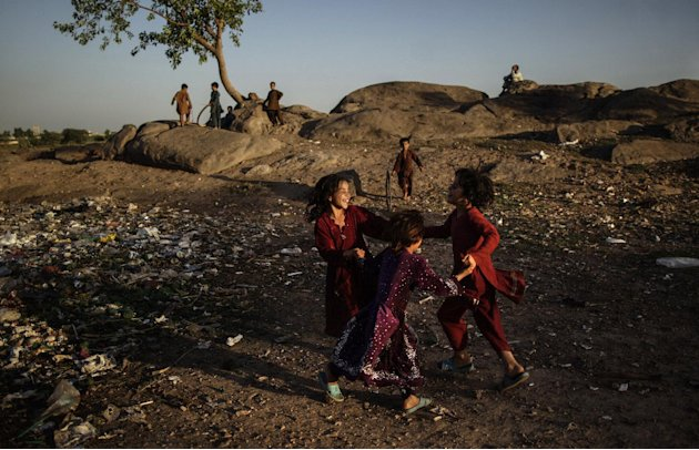 Afghan refugees play in a field on the outskirts of Islamabad, Pakistan, Tuesday, June 18, 2013. Pakistan hosts over 1.6 million registered Afghans, the largest and most protracted refugee population
